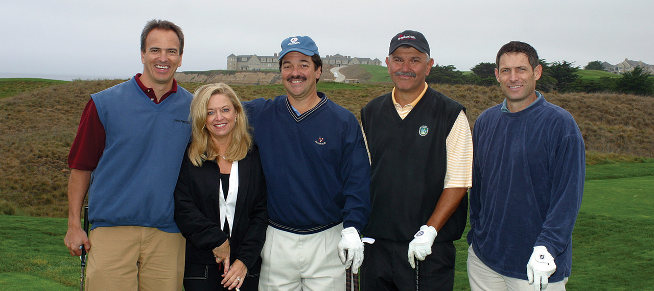 Golfers posing for photo with Steve Young