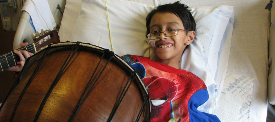 Boy playing drum on hospital bed