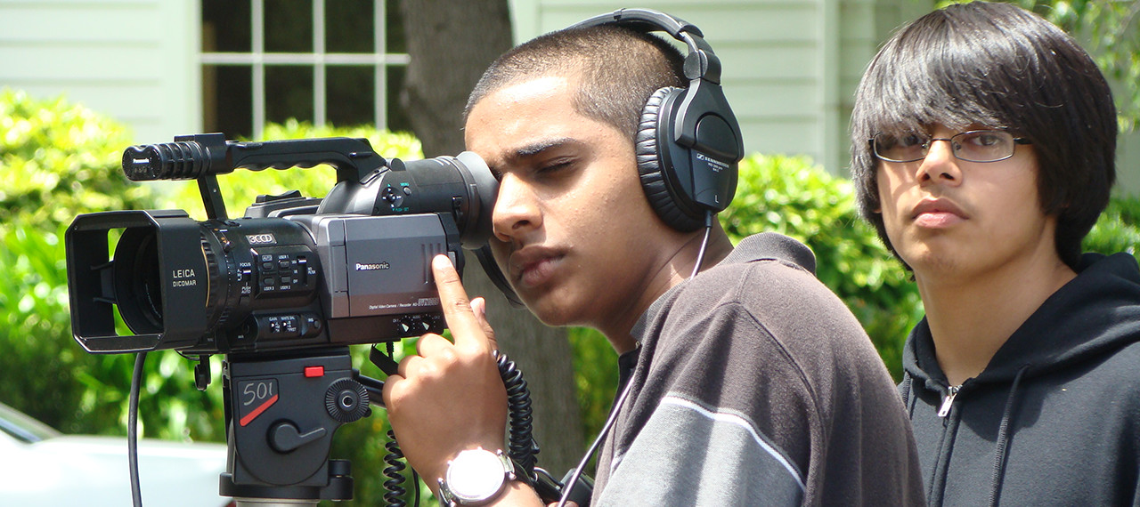 Boy focuses on using video camera