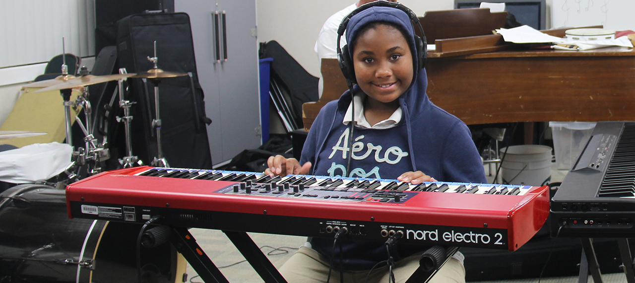 Smiling girl plays keyboard