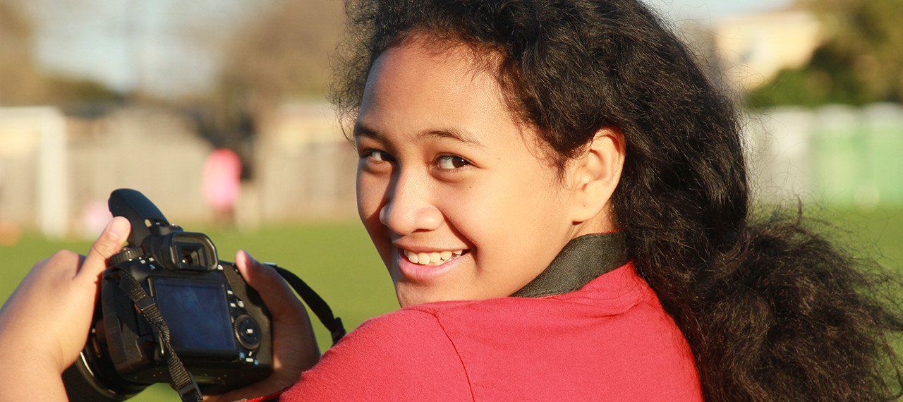 Girl smiles while holding camera