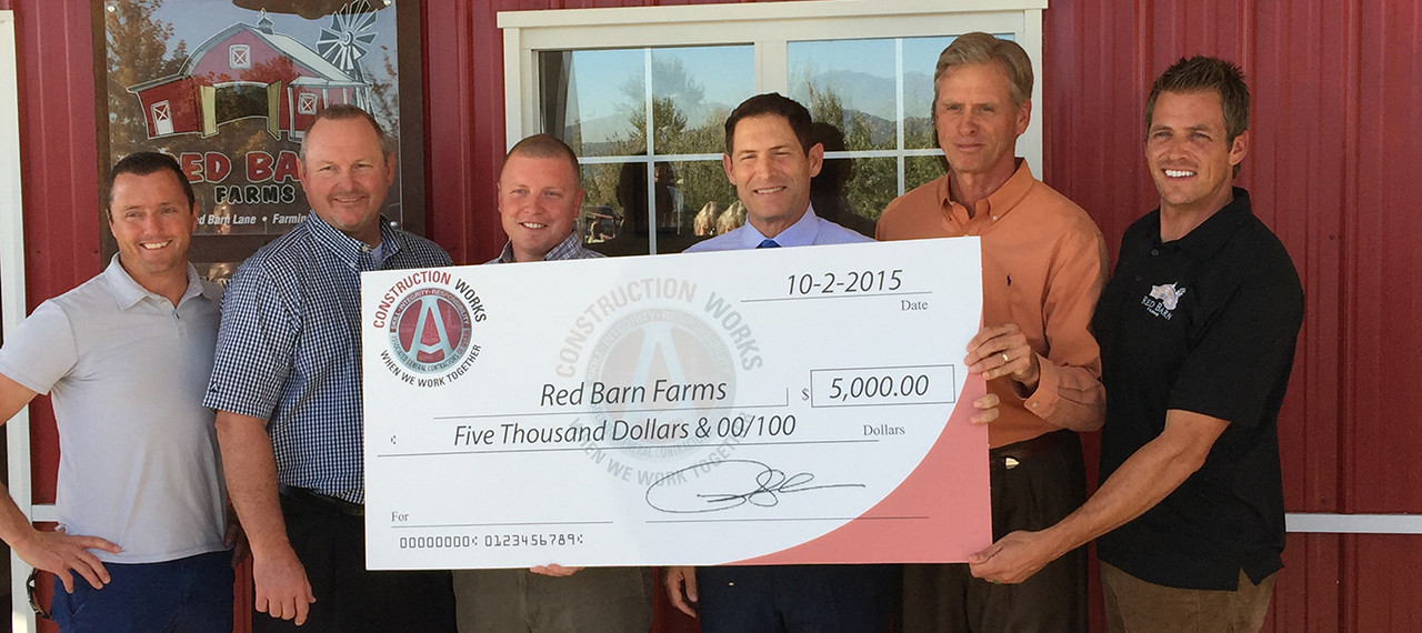 Steve Young presents $5,000 check to Red Barn Farms
